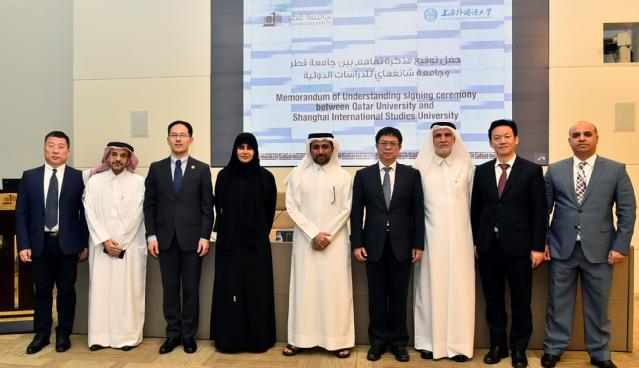 a photo of the visiting delegation and QU officials signing a MOU between QU and Shanghai International Studies